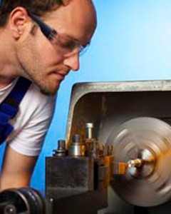 Close-up of technician working on lathe machine